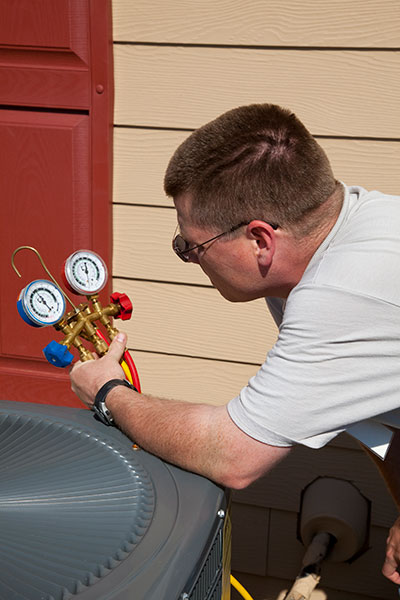 ac technician checking refrigerant levels